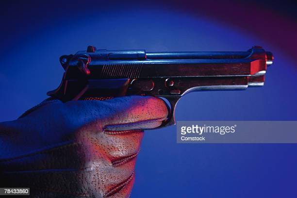Gloved hand aiming gun