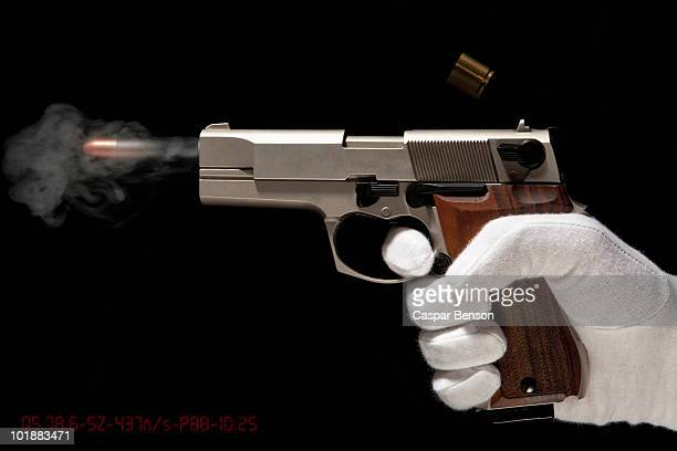 a gloved hand firing a gun - shooting a weapon stock pictures, royalty-free photos & images