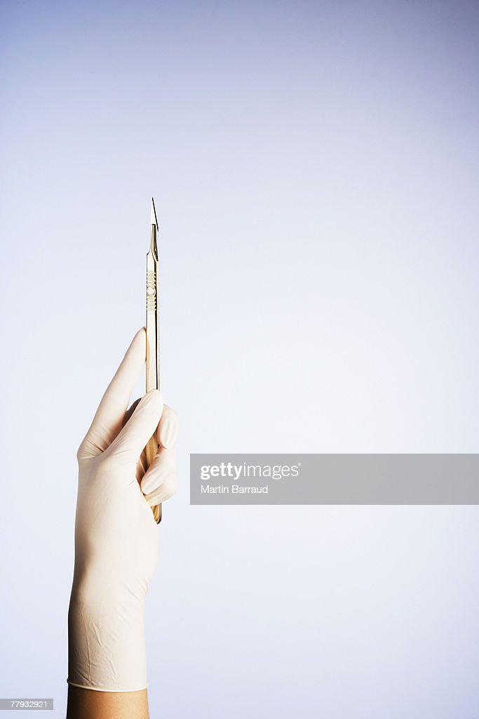 A gloved hand holding a scalpel : Stock Photo