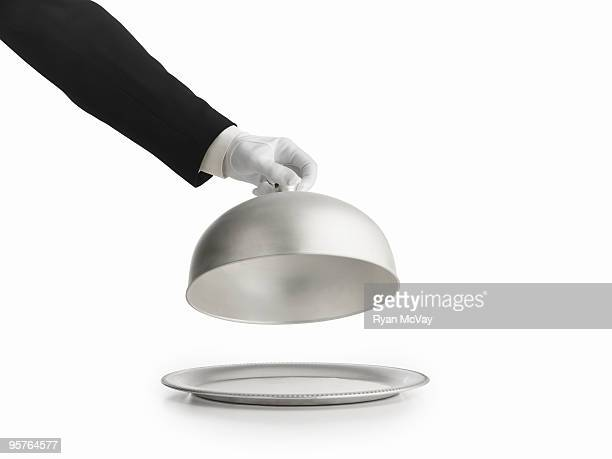 gloved hand lifting silver lid off a platter