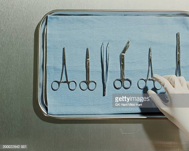 Gloved hand reaching for surgical scissors on metal tray