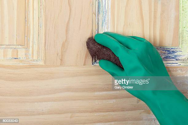 Gloved hand using metal wool to remove paint from a door