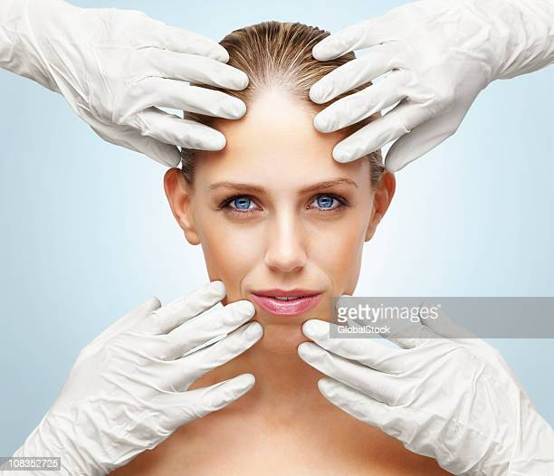 Gloved hands examining woman's face against blue background