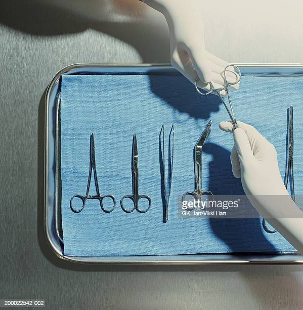 Gloved hands passing surgical scissors