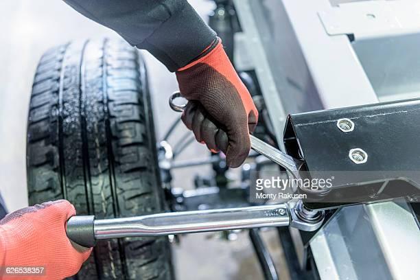 gloved hands using spanner and ratchet on automotive production line - monty rakusen stock-fotos und bilder