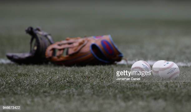 Gloves and balls are seen on the field before the Chicago Cubs take on the Atlanta Braves at Wrigley Field on April 13 2018 in Chicago Illinois The...
