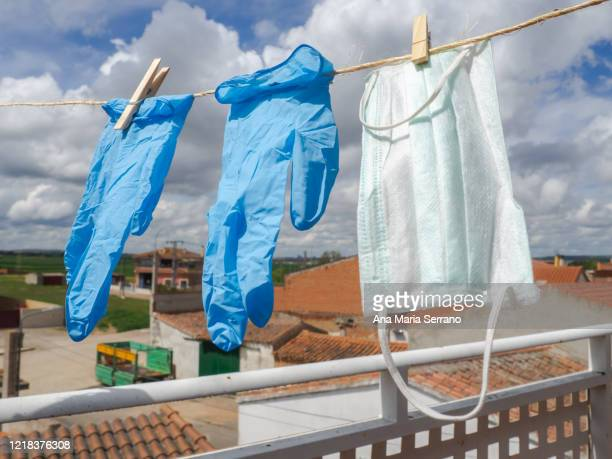 gloves and protective face masks hang out a clothesline rope against a sky with storm clouds - world health organisation stock pictures, royalty-free photos & images