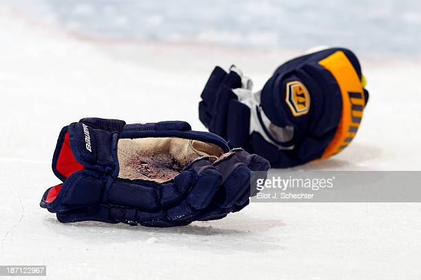 Gloves belonging to Erik Gudbranson of the Florida Panthers and Cody McCormick of the Buffalo Sabres sit on the ice at the BBT Center on October 25...