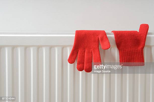 gloves drying on a radiator - radiator heater stock photos and pictures