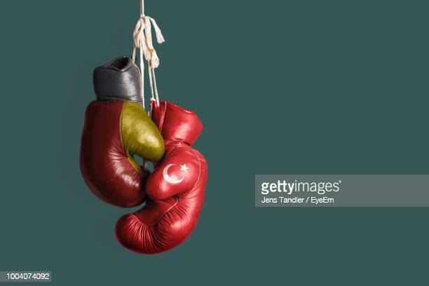 gloves hanging against green background - boxing gloves stock pictures, royalty-free photos & images