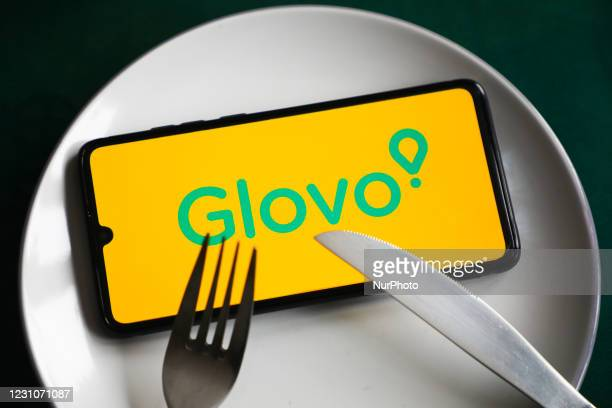 Glovo app logo is displayed on a mobile phone screen photographed for illustration on a plate and with cutlery. Krakow, Poland on February 9, 2021....