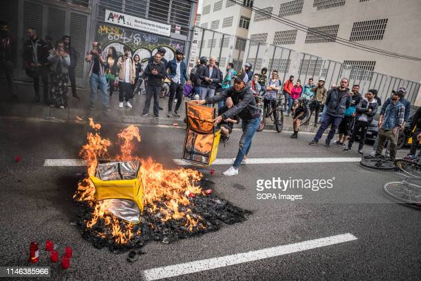 Glovo delivery boy is seen throwing his work bag to the bonfire during the protest A group of food on demand couriers service workers of the company...
