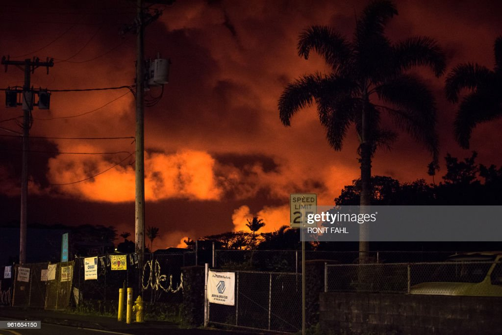 TOPSHOT - Glow from the lava in the Leilani Estates and Lanipuna Gardens subdivisions is seen from Pahoa, Hawaii on May 22, 2018. - Authorities in Hawaii have warned of dangerous 'laze' fumes as molten lava from the erupting Kilauea volcano reached the Pacific Ocean. Two lava flows 'reached the ocean along the southeast Puna coast overnight,' on Hawaii's Big Island, the US Geological Survey, which monitors volcanoes and earthquakes worldwide, said in a statement May 20, 2018.