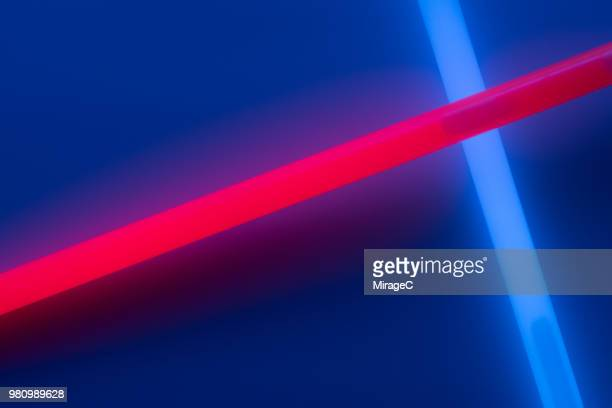 glow sticks crossing on deep blue - neon stock pictures, royalty-free photos & images