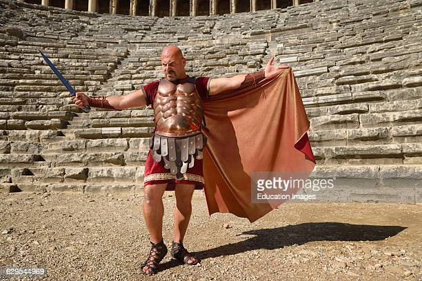 Glowering Roman Gladiator with sword spreading cape in sun on stage at the ancient Aspendos theatre Turkey