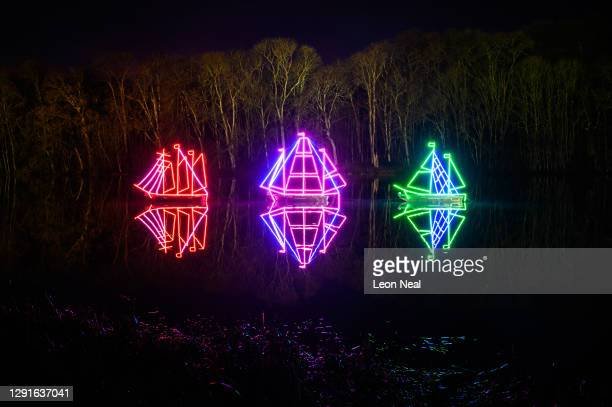 Glowing boats are reflected in the lake as part of the annual Illuminated Lights Trail at Blenheim Palace on December 15, 2020 in Woodstock, England....