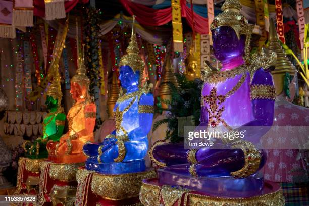 glowing buddha statues. - tim bewer stockfoto's en -beelden