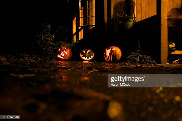 glowing carved halloween pumpkins in back yard at night, usa - focus on background stock pictures, royalty-free photos & images