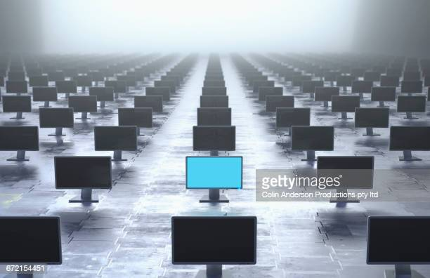 Glowing computer monitor in row of monitors