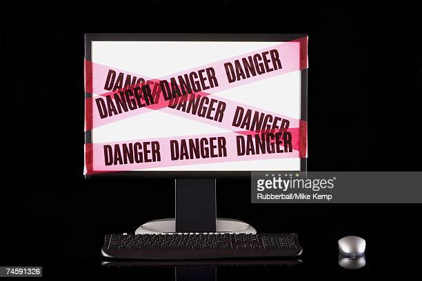 Glowing computer monitor with danger tape