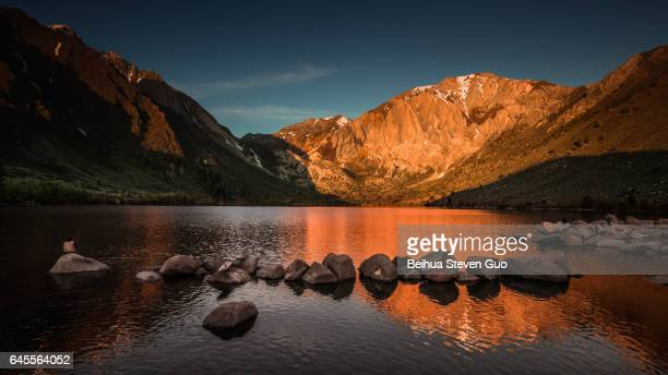 Glowing Convict Lake Sunrise in the Eastern Sierra, California, with Fisherman Sitting on a Rock in the Foreground