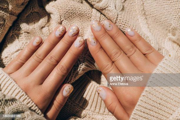 glowing hands in sweater with knitted sleeves and with nude color manicure with gold particles on knitted background. trendy colors of the year - long sleeved stock pictures, royalty-free photos & images