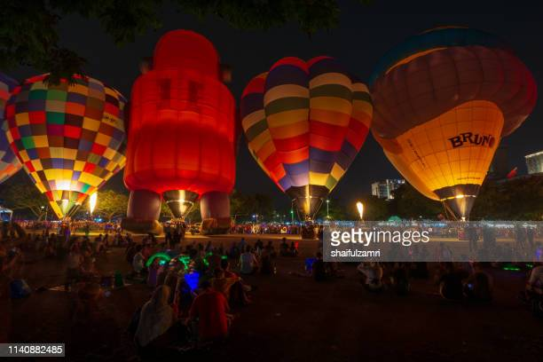 glowing hot balloons brightening the night - shaifulzamri stock pictures, royalty-free photos & images