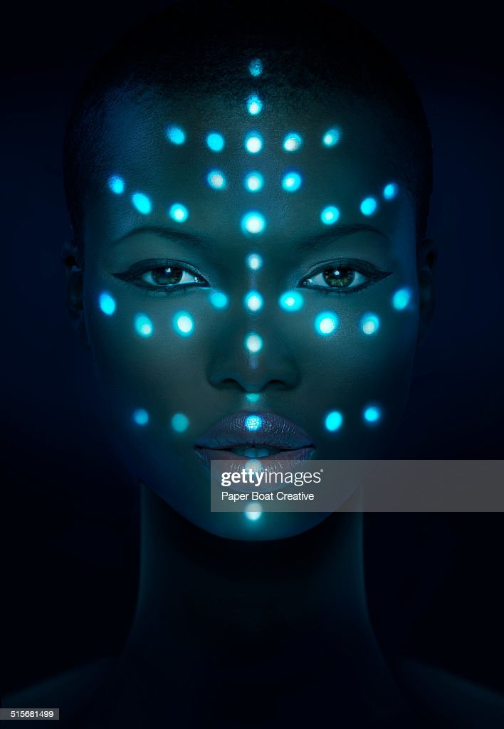 Glowing laser beam dots on a woman's face : Stock Photo