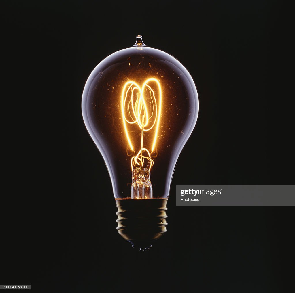 Glowing Light Bulb On Black Background High-Res Stock ...