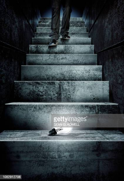 glowing light bulb on steps - at the bottom of stock pictures, royalty-free photos & images