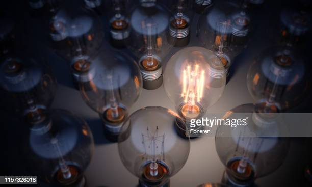 glowing light bulb standing out from the crowd - light bulb stock pictures, royalty-free photos & images