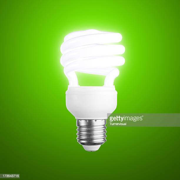 glowing lightbulb on green + clipping path - energy efficient lightbulb stock photos and pictures