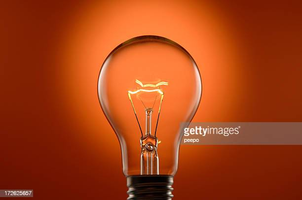glowing lightbulb on orange background - filament stock photos and pictures