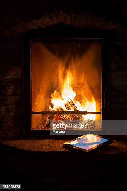 glowing log fire and digital tablet on hearth - warming up stock pictures, royalty-free photos & images