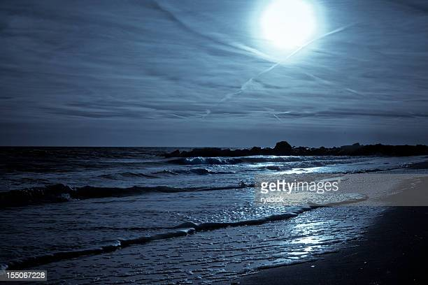 Glowing Moon Through Wispy Clouds Reflecting on Beach Shore