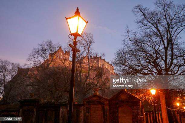 Glowing old-fashioned street light at dusk with Edinburgh Castle, Castle Rock in the background