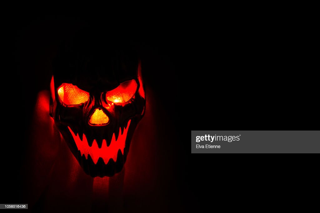 Glowing orange light through a Halloween mask against a dark background : Stock Photo