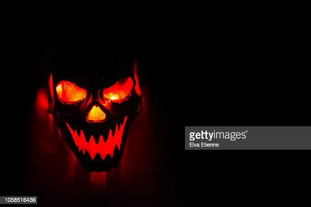 glowing orange light through a halloween mask against a dark background - halloween scary stock pictures, royalty-free photos & images