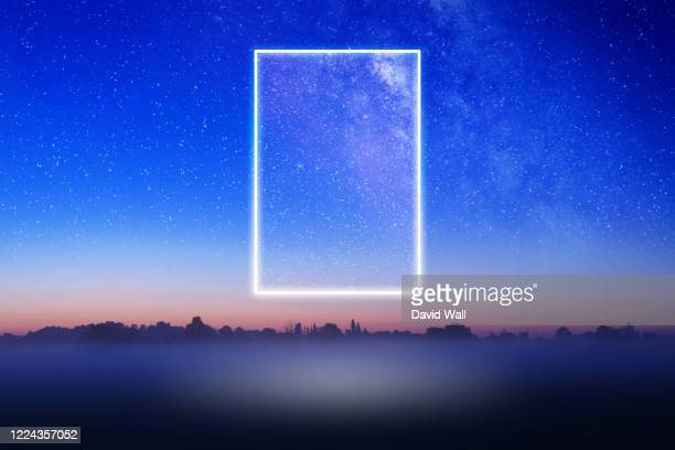 a glowing, portal, gateway floating above a misty field with a galaxy of stars behind. science fiction concept. - futuristic stock pictures, royalty-free photos & images