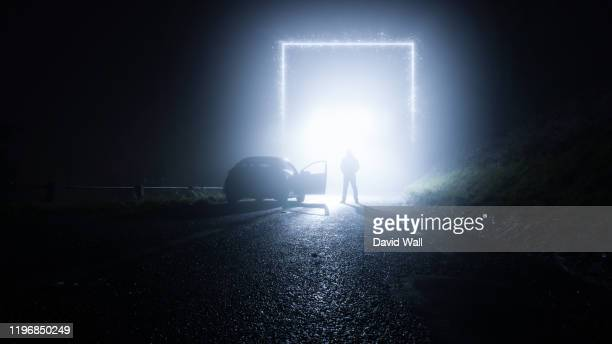 a glowing, portal, gateway on a country road. with a man standing next to a car. on a spooky, foggy, winters night. science fiction concept. - magic doors stock pictures, royalty-free photos & images