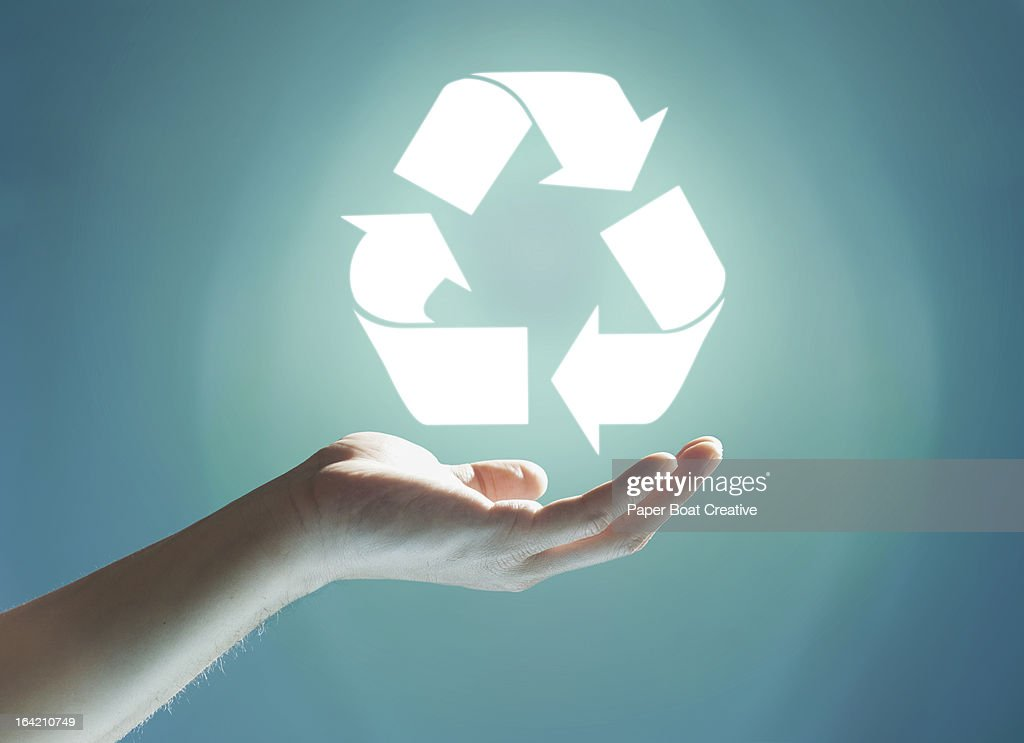 Glowing recycling sign floating above hand : Stock Photo
