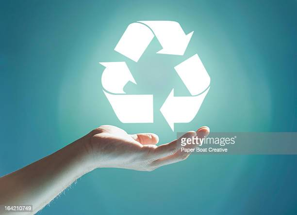glowing recycling sign floating above hand - recycling stock-fotos und bilder