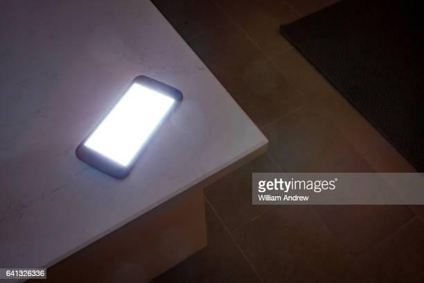 glowing smartphone on countertop at night - bancada de cozinha mobília - fotografias e filmes do acervo