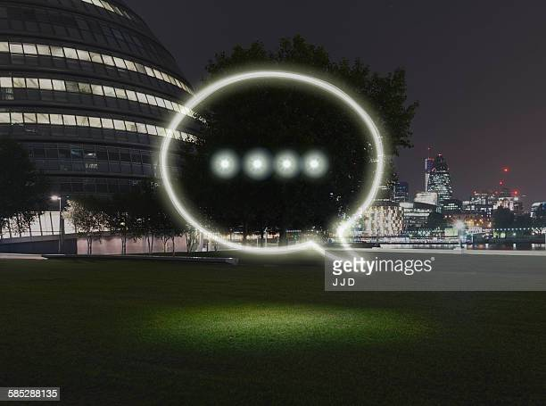 Glowing speech bubble symbol in city at night