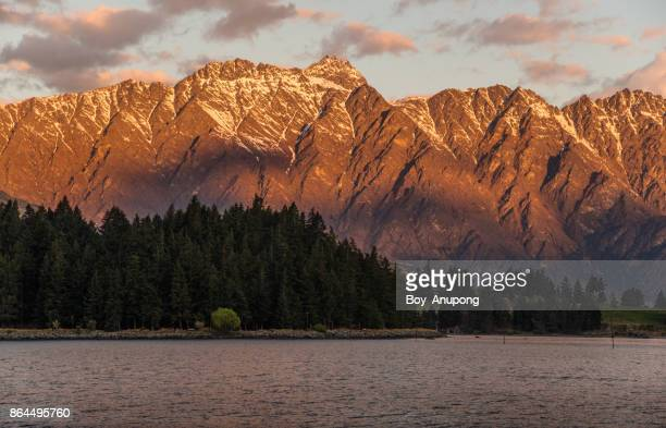 glowing sunset lighting with the remarkables mountain range in queenstown, new zealand. - the remarkables stock-fotos und bilder