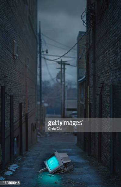 Glowing television in abandoned urban alleyway