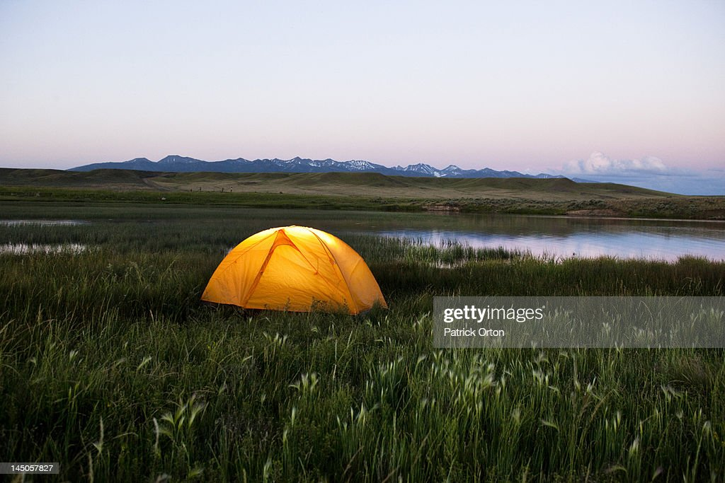 A glowing tent next to a lake at sunset in Montana. : Stock Photo