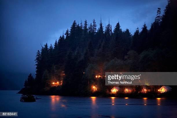 Glowing tents along coastline at night.
