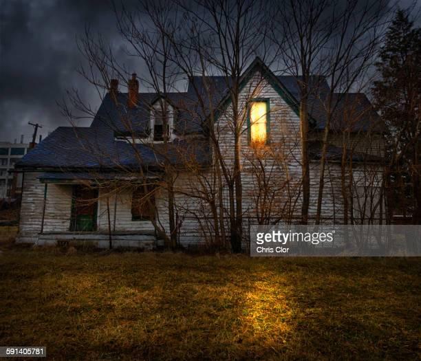 Glowing window casting light in backyard