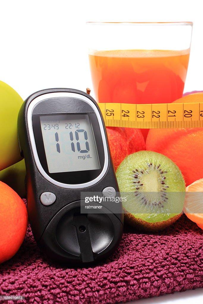 Medidor de glicose, frutas, fita métrica e Copo de Suco : Foto de stock